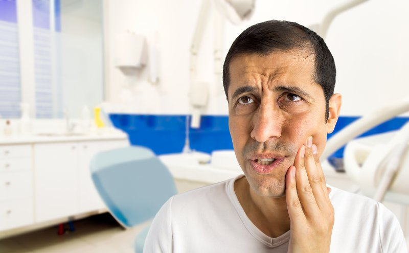 a middle-aged man holding his cheek in pain as a result of a dental injury