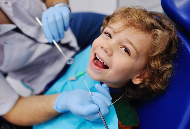 a little boy smiling while preparing to undergo a dental checkup and cleaning