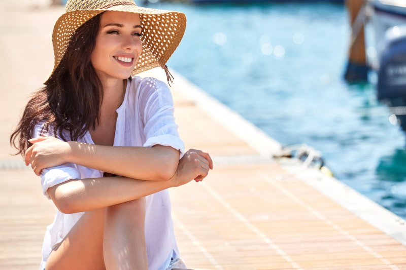 a young woman sitting by the pool wearing a wide-brimmed hat and showing off her healthy, beautiful smile