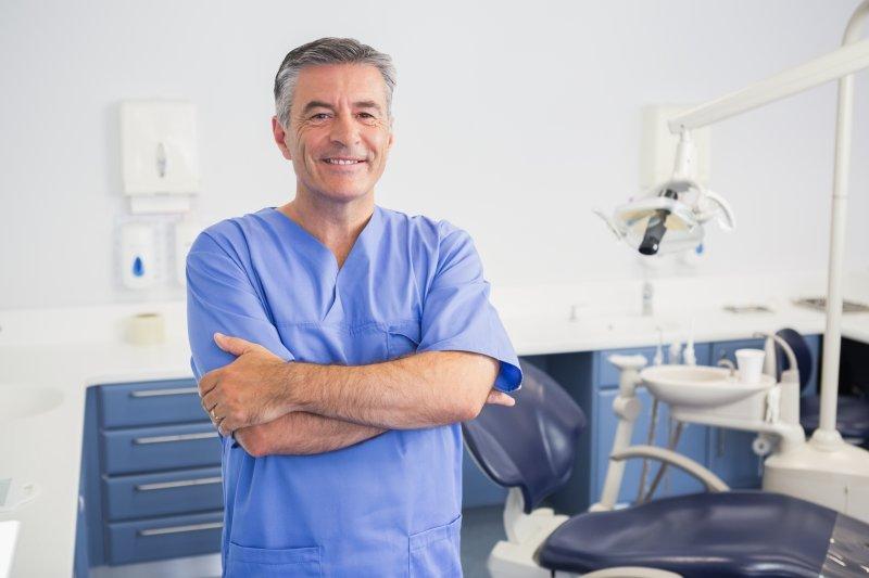 a male dentist wearing his scrubs inside a treatment room
