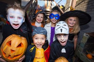 A group of kids dressed in Halloween costumes.