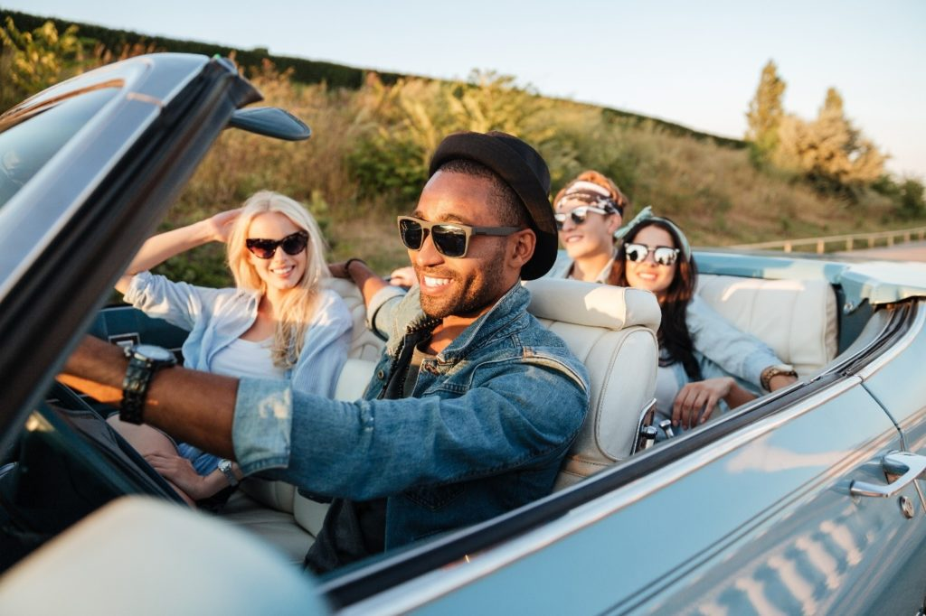 Group of friends smiling on a road trip