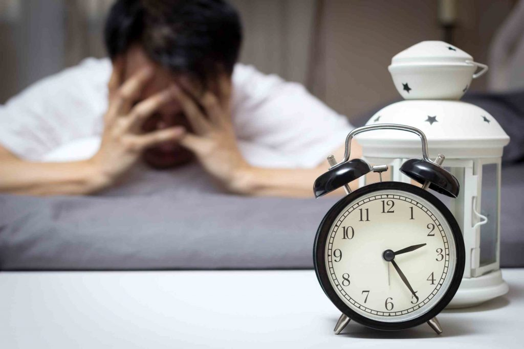 Frustrated man with his alarm clock ringing